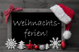 Black And White Blackboard With Red Santa Hat And Christmas Decoration like Snowflake, Tree, Christmas Ball, Fir Cone, Star. German Text Weihnachtsferien Means Christmas Holiday. Wooden Background